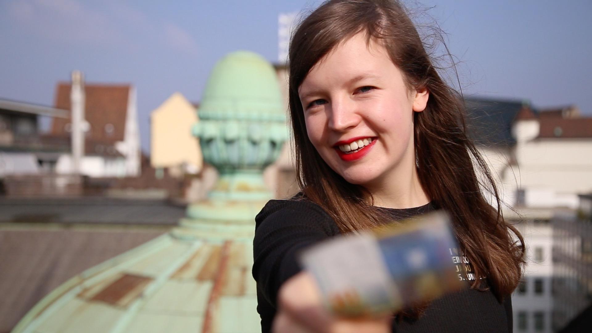 Eine junge Frau hält einen Flyer in die Kamera
